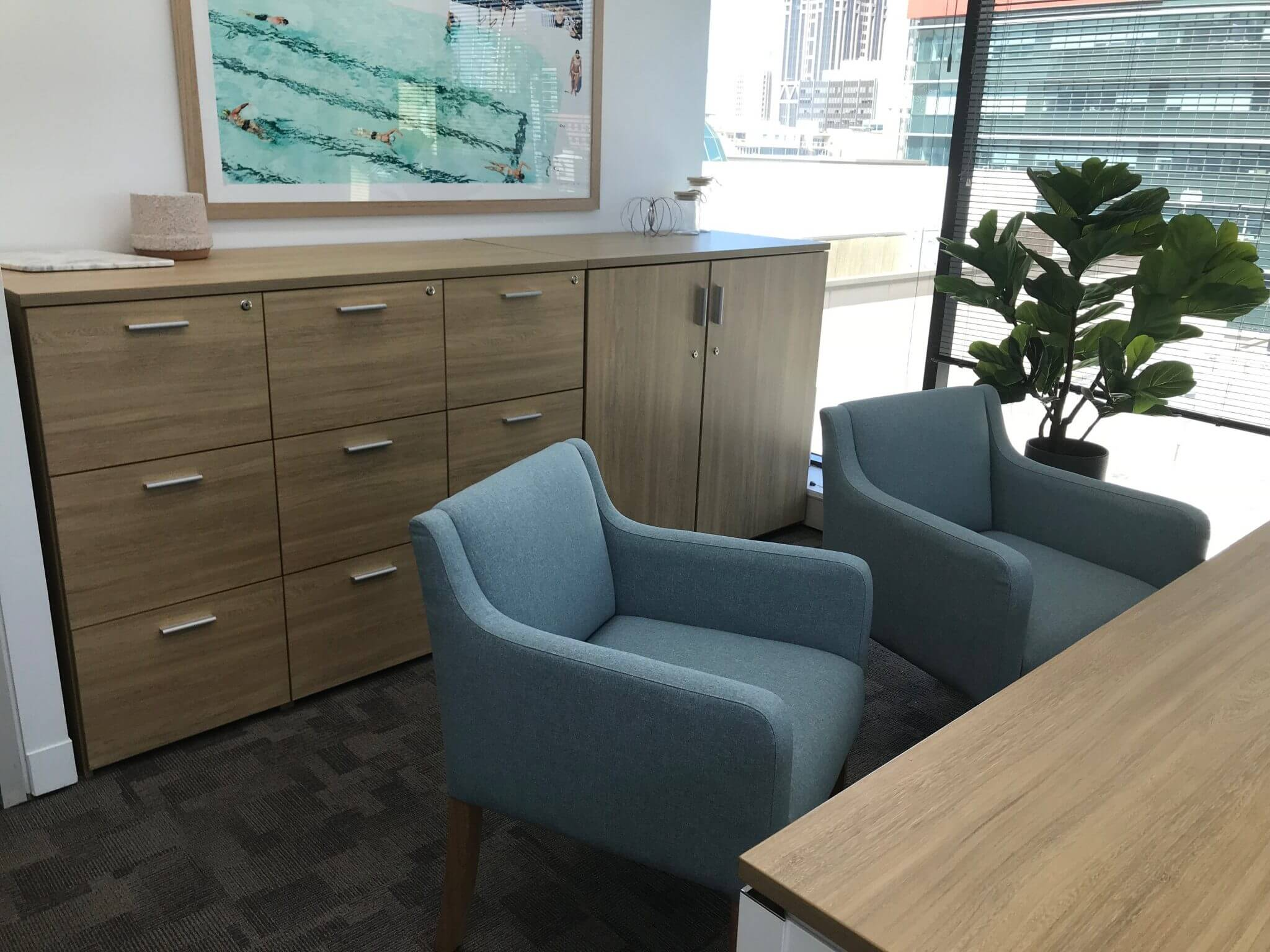 woodgrain Laminex office desk and credenza with two blue upholstered chairs