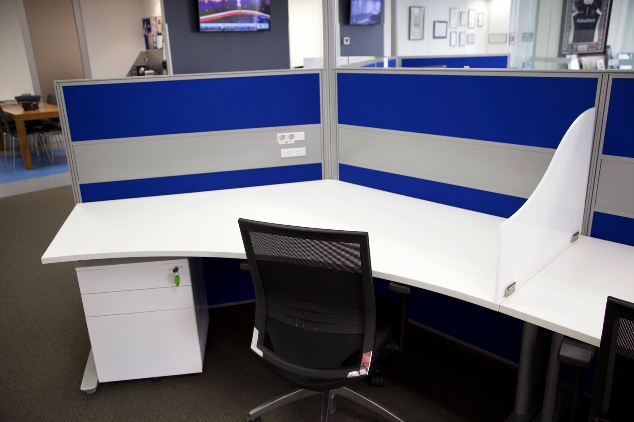 Black office chair pushed up to a white desk with a blue free-standing office partition on one side