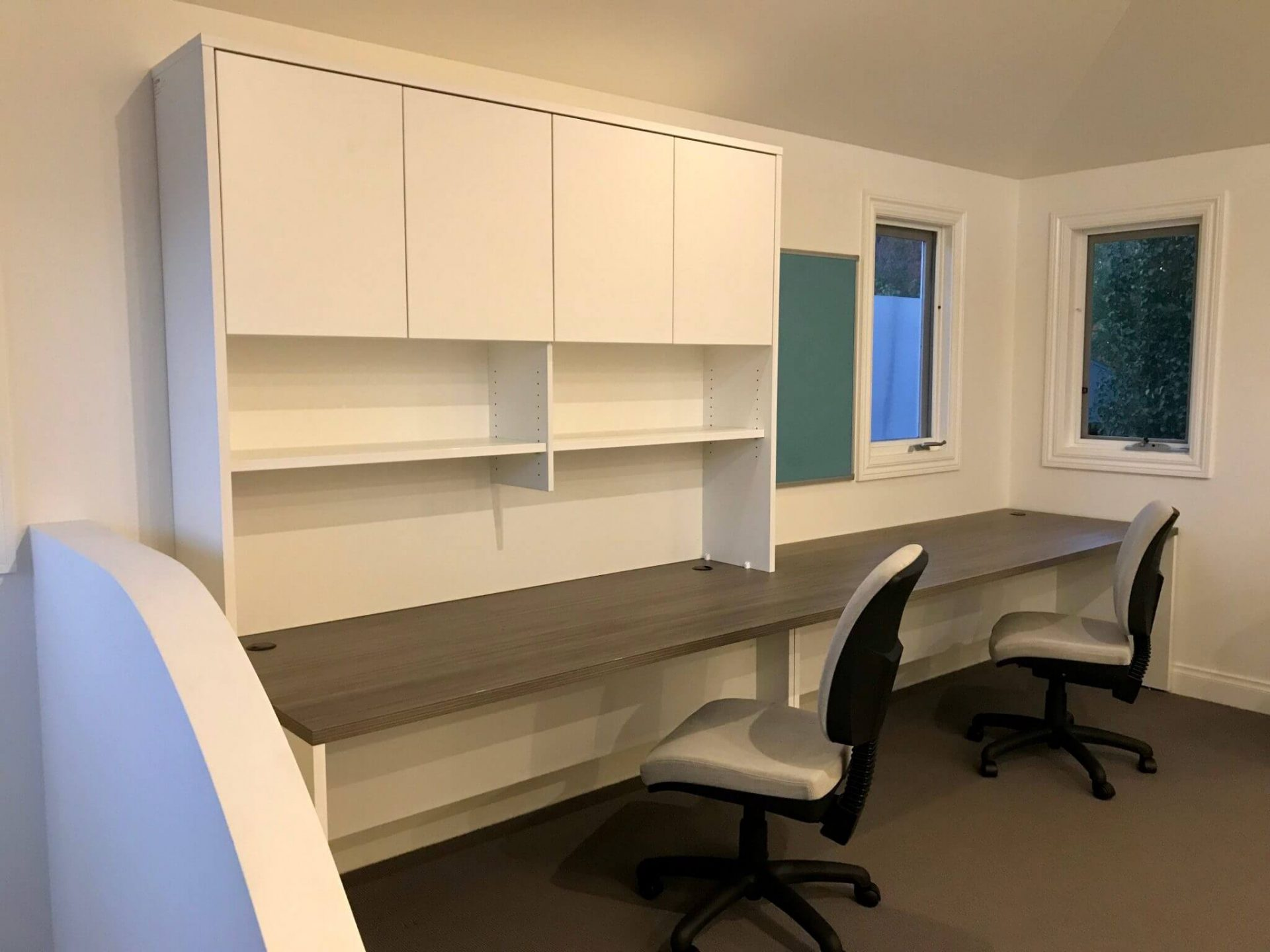 Home office with long desk and hutch and two grey office chairs