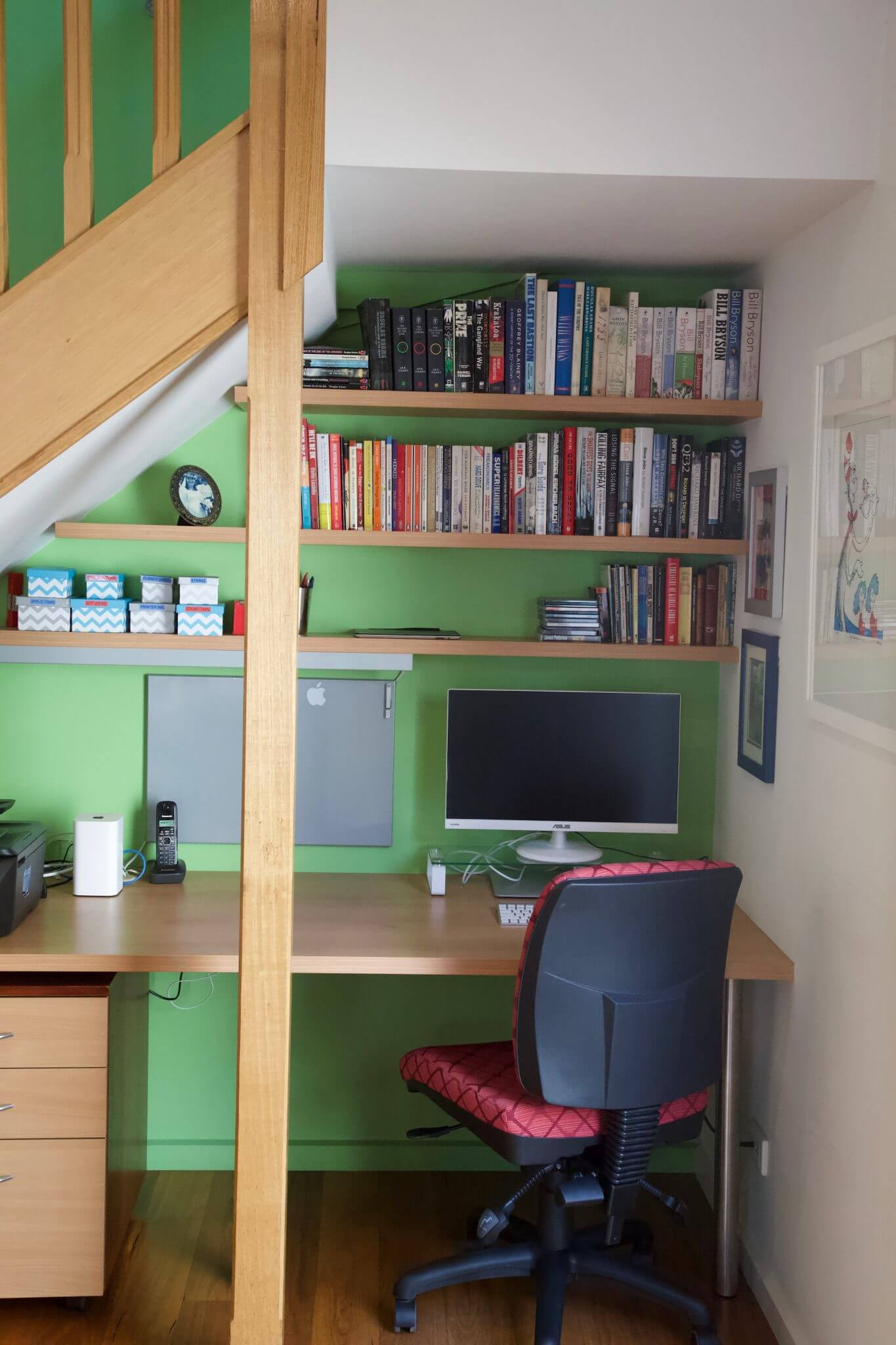 Study nook under stairs with computer desk and three shelves of books